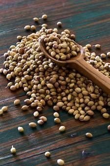 色付きの素朴な背景にスプーンで有機乾燥コリアンダーの種子。