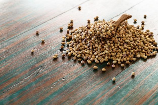 色付きの素朴な背景にスプーンで有機乾燥コリアンダーの種子(コリアンダー)。
