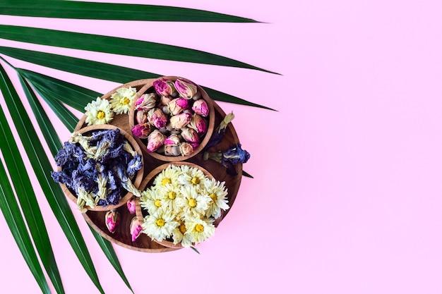 ピンクの背景に分離された木製のボウルに乾燥茶の品揃え。