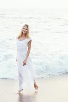 アジアの砂の熱帯のビーチで長い白いドレスの魅力的な幸せな成熟した観光ブロンドの女性。