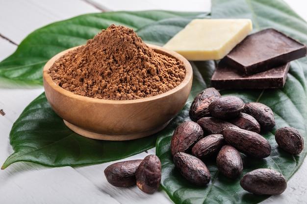 木製ボウルのカカオパウダー、カカオ豆全体、ダークビターチョコレートの小片、元の新鮮な葉のココアバター
