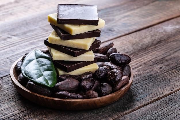 古い素朴なテーブルにカカオ豆全体とダークチョコレートとココアバター