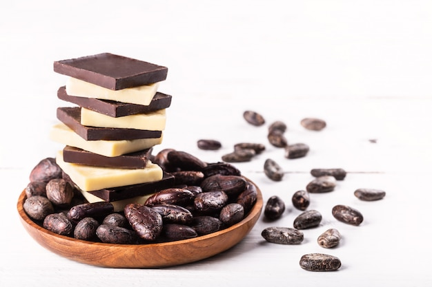 古い素朴な白いテーブルに生のダークビターチョコレートとカカオ豆とカカオバターのスタック。