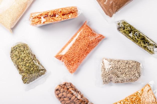 白い壁にプラスチック製のラップでカラフルな様々な穀物、種子、ナッツ、マメ科植物のグループ。健康的なタンパク質製品。
