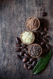 カカオ製品-古い素朴な壁にパウダー、バター、全粒粉、ペン先、オリジナルの葉。