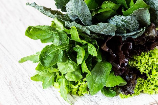 緑と赤のレタス、ルッコラ、ケール、アマランス、ほうれん草の白いテーブルの上の葉