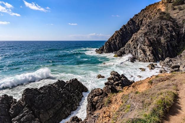 Скалистый пляж с видом на море и мыс байрон-бей