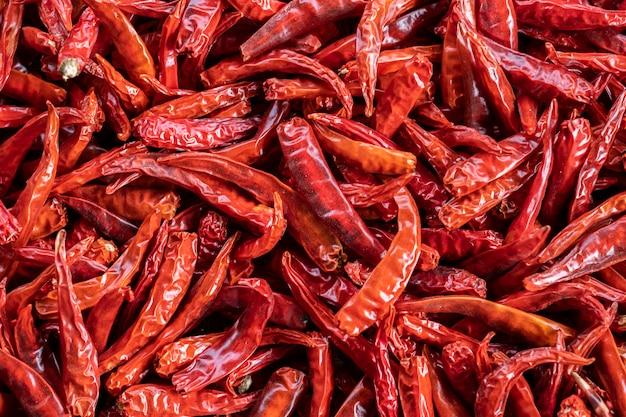 チリ味のスパイシーさ、美しいカラフルな鮮やかな赤い色を強調するために太陽の下で乾燥されている赤いタイホットチリペッパーのトップビュー山を閉じます