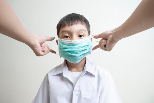 孤立したアジアの学校の子供男の子の子供親が顔の鼻の口、コロナウイルス病、細菌、空気からの感染からの保護の概念をカバーする上で緑のマスクを正しく置くのを助ける
