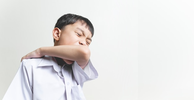 咳をしながら肘を使って顔の口を覆うアジアの学校の子供男の子、コロナウイルス病、細菌および空気感染からの保護のための正しい方法の概念