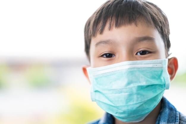 顔の鼻の口、コロナウイルス病、細菌および空気感染からの保護の概念をカバーする緑のマスクを身に着けているアジアの子供男の子の顔を間近で分離