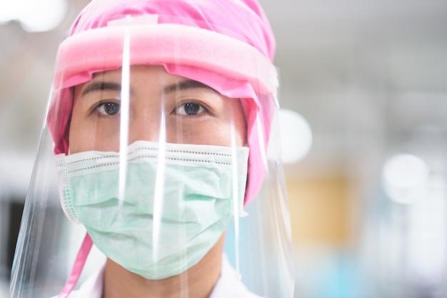 Женщина-врач медсестра носить защитную одежду из хирургической маски и щитка
