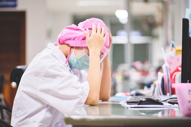 コンピューターの前で一生懸命働いてストレスや頭痛の下で女医