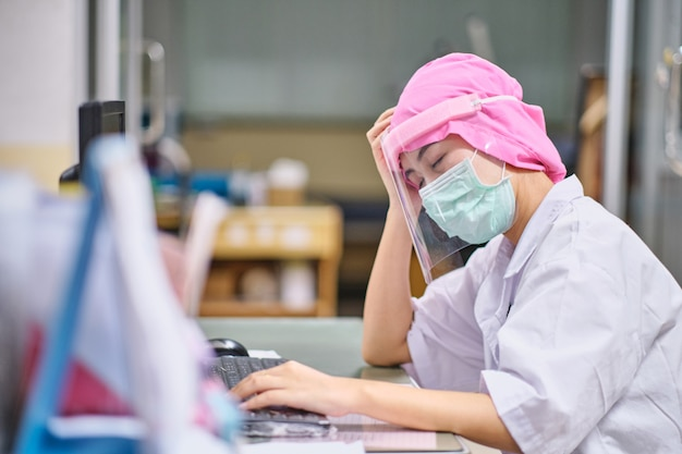 コンピューターの前で寝ているストレスと頭痛の下で女医