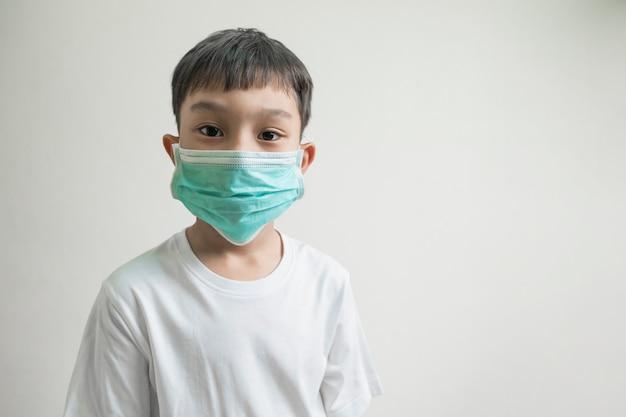 顔の鼻の口、コロナウイルス病、細菌、空気感染からの保護の概念を覆う緑色のマスクを身に着けている孤立したアジアの子供男の子子供