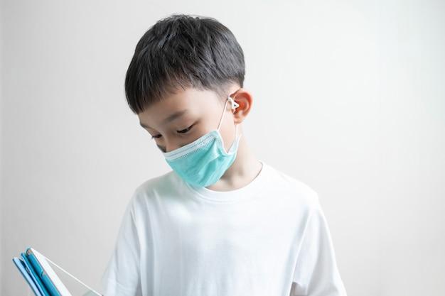 タブレットデバイス、コロナウイルス病、細菌および空気感染からの保護の概念で遊んで顔の鼻の口を覆っている緑のマスクを身に着けている孤立したアジアの子供男の子子供