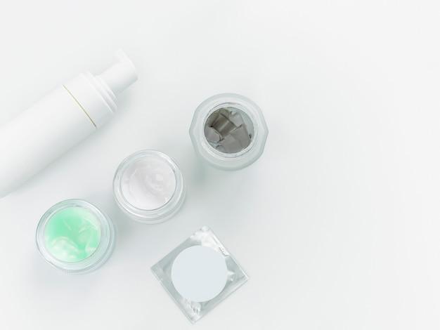 白い背景の上のガラスの瓶にスキンケア製品とハーブスパ皮膚科化粧品衛生クリーム。