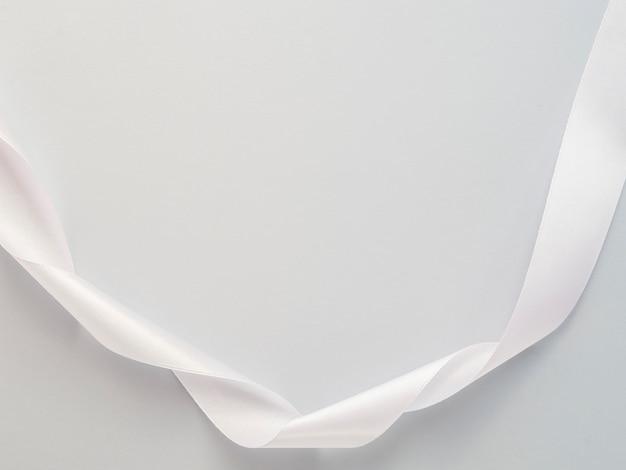 Пастельная сладкая белая атласная бант лента на белом фоне.