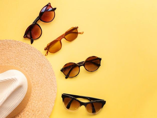 Соломенная женская шляпа с солнцезащитными очками, вид сверху ярко-желтый фон, плоская планировка, одиночка