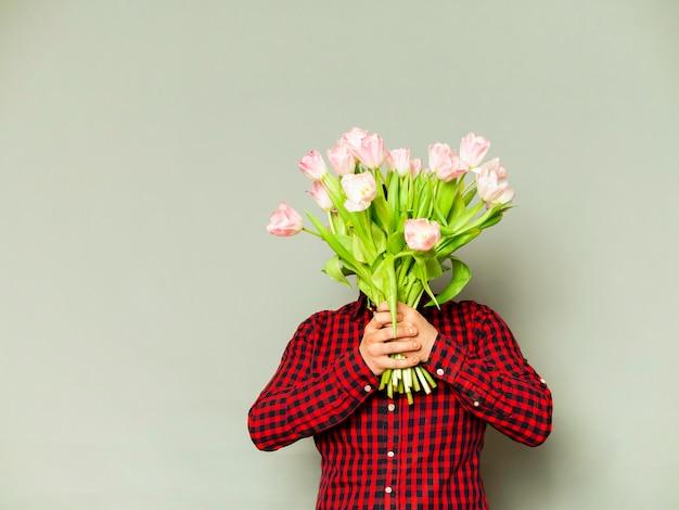 灰色に分離された美しい花束を持って配達人