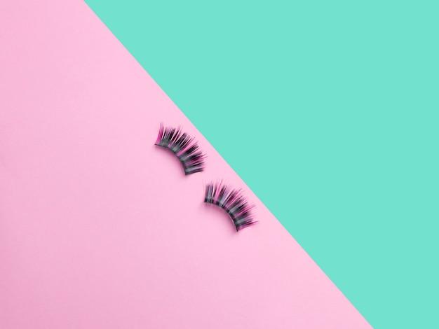 Длинные цветные волоски ресниц. плоская композиция с накладными ресницами на розовом и бирюзовом фоне