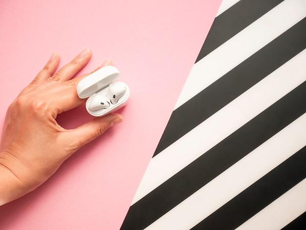 Белые наушники с чехлом на черном и розовом
