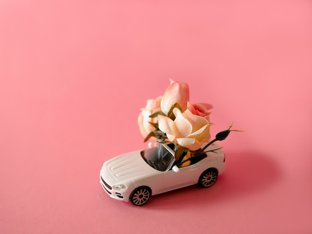 ピンクの背景にバラの花束を提供する白いおもちゃの車