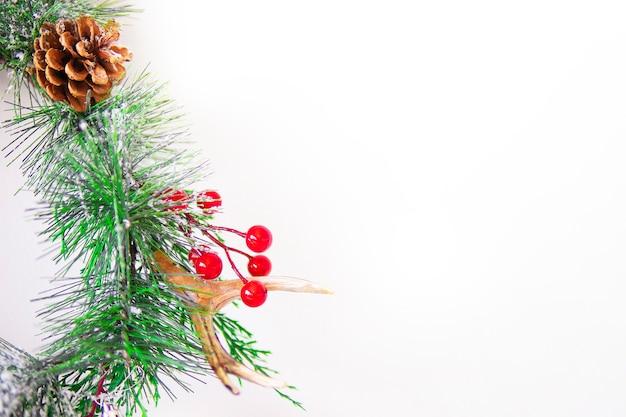 赤い果実と白い背景の上の松ぼっくりのクリスマスの素敵な花輪。クリスマスの家の装飾。新年のグリーティングカード。メリークリスマスと新年あけましておめでとうございます家族の休日祭りのコンセプト、フラットレイアウト