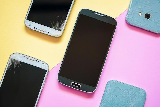 ピンクと黄色の壊れたガラス画面を持つモバイルスマートフォン。