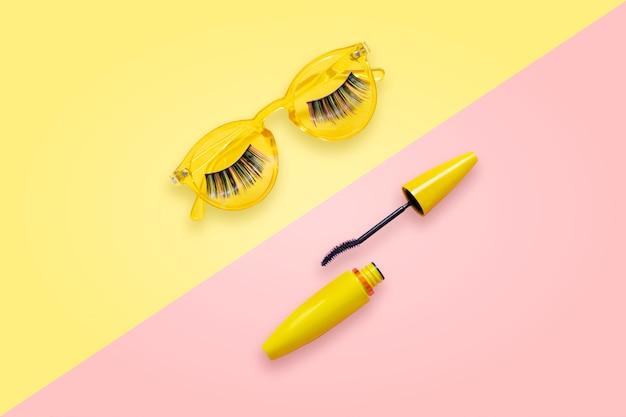 偽まつげ付きのピンクと黄色のサングラスに開いたブラシと黄色のチューブのマスカラ。