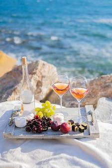 Пляжная морская сцена летний пикник с розовым вином и виноградом, зефиром, ягодами.