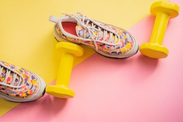 女性ランニングスニーカーとダンベルイエローピンクの背景を持つアスリートのセット。フィットネスの概念。ジムおよび家庭用機器