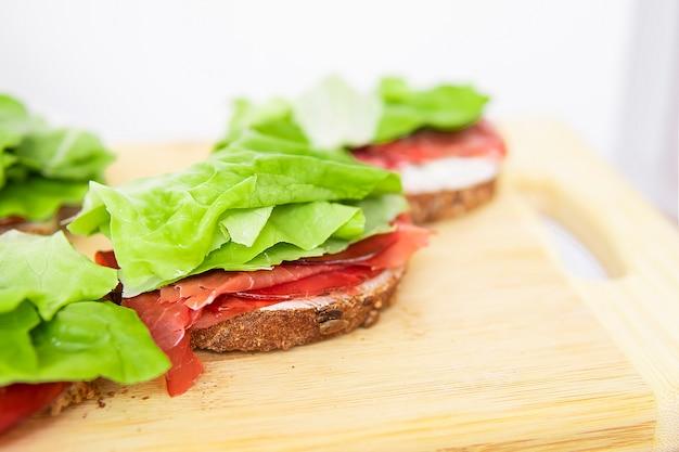 朝食のおいしい自家製サンドイッチ。適切な栄養摂取。カロリーバランス。
