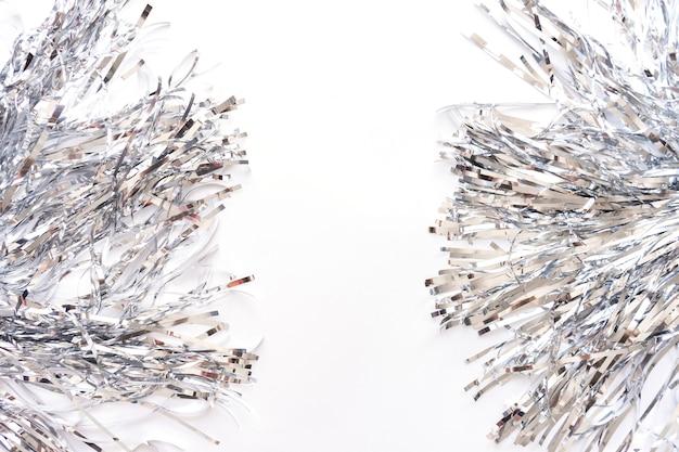 Серебряные полосы сусали фольги металла изолированные на белой предпосылке, рождестве или праздничной гирлянде украшения.