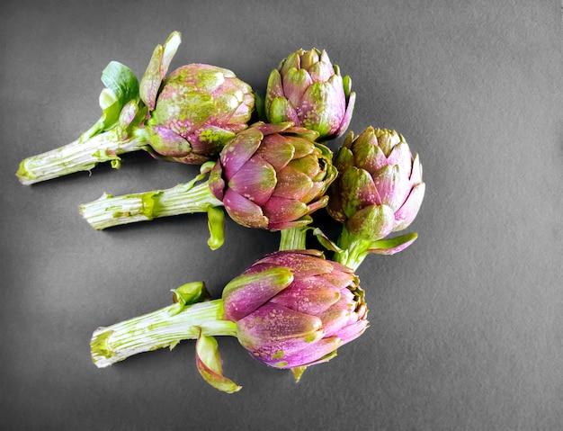 灰色の背景にアーティチョーク。上からの眺めと新鮮な有機アーティチョークの花