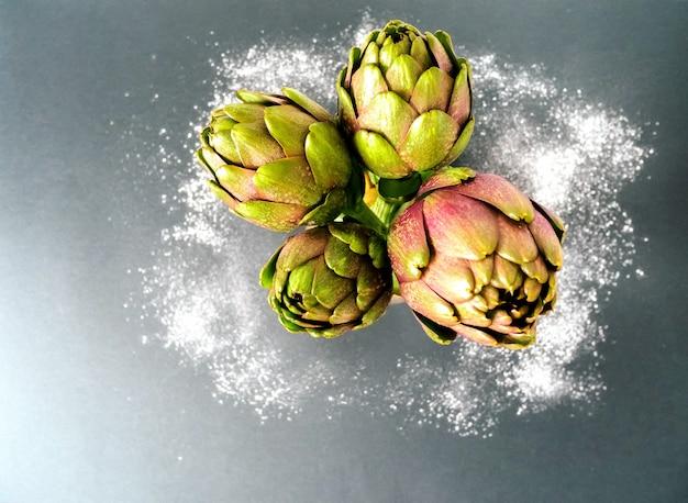 灰色の背景にアーティチョーク。上からの眺めと小麦粉の周りの新鮮な有機アーティチョークの花