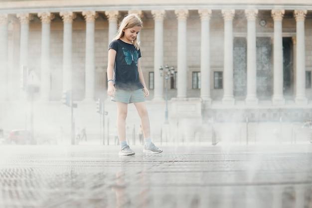 Девушка прогуливается по площади с водяными струями на фоне старого здания с колоннами