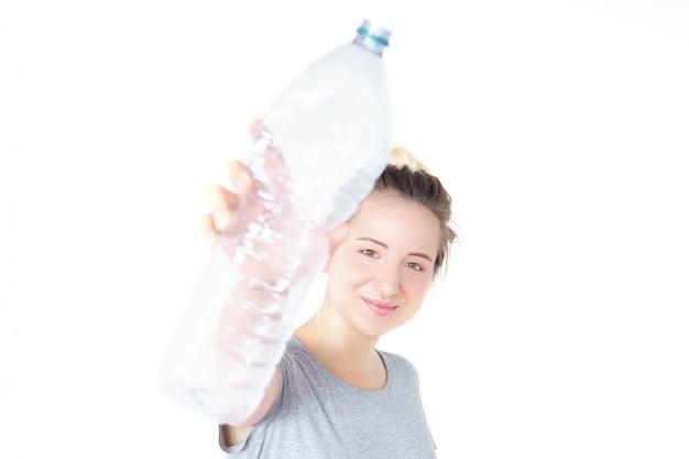 幸せな女を示し、分離されたリサイクル可能なペットボトルを保持しています。ぼやけた効果。リサイクルの概念。廃棄物分別収集