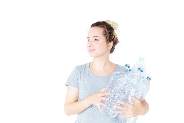Счастливая женщина показывает и держа рециркулируемую пластичную бутылку изолированный. размытый эффект. концепция утилизации. отдельный сбор отходов