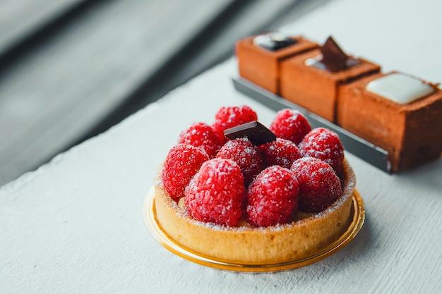 フルーツとベリーのタルトデザートトレイとチョコレートが分離されました。新鮮な天然ラズベリーと美しいおいしい菓子菓子のクローズアップ。菓子。パン屋さんのデザイン要素。