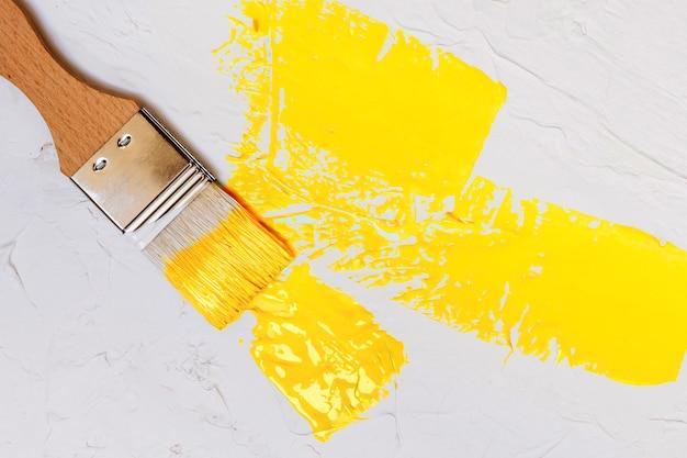 Кисть с цветной краской на белом фоне стены