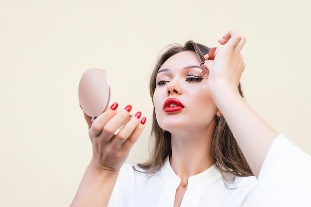 ベージュ色の背景に磁気偽まつげを保持しているふっくらした赤い唇を持つ女性