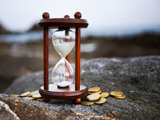 岩の背景にコインと砂時計の形を流れる砂。時間の投資と退職者の節約