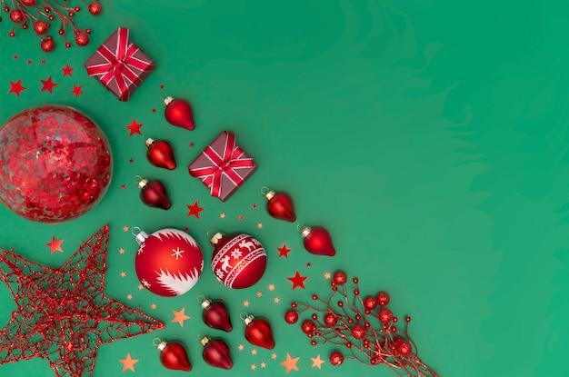 緑のエメラルドの背景に赤のクリスマスと新年のおもちゃ