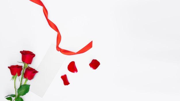 赤いバラ、赤いリボンと分離された花びらと銀の空白