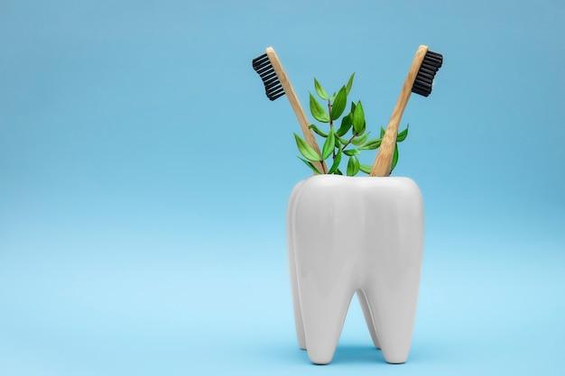 緑の枝を持つ竹木製歯ブラシは、歯の形で白い歯ブラシホルダーに残します歯科医療の概念。コピースペース。エコフレンドリーグッズ