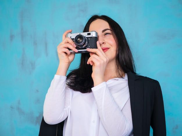 カメラマンクローズアップ肖像画ヘッドショットレトロなビンテージカメラで写真を撮る若い女性