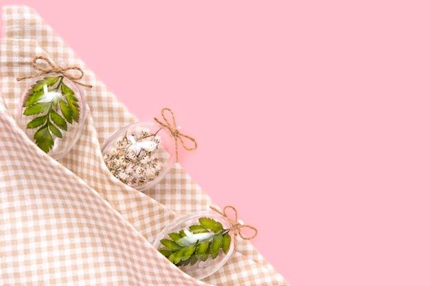 ピンクの背景にナプキンで白い花、緑のシダの葉で満たされた透明なガラスの卵をイースター国境組成。エコスタイリッシュな装飾の概念。コピースペース。お祝いフラットレイアウトグリーティングカード