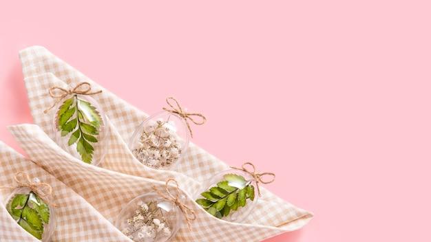 ピンクの背景にナプキンで白い花、緑のシダの葉で満たされた透明なガラスの卵をイースター国境組成。エコスタイリッシュな装飾の概念。コピースペース。お祝いバナーグリーティングカード