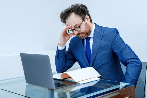 Бизнесмен с продуманным лицом в синем костюме, используя ноутбук на фоне интерьера офиса. концепция придумать новую стратегию, антикризисный план